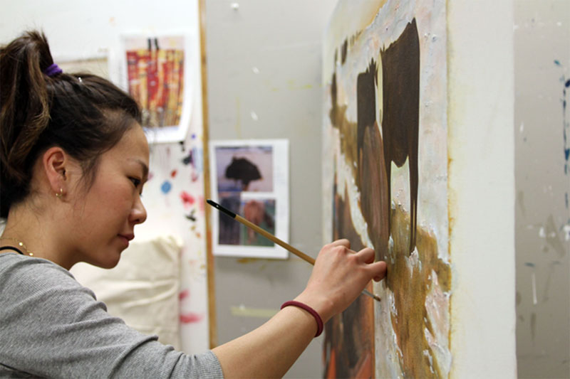 Third year visual arts student Jihyun Choi works on her latest painting. Photo by Megan Narsing.
