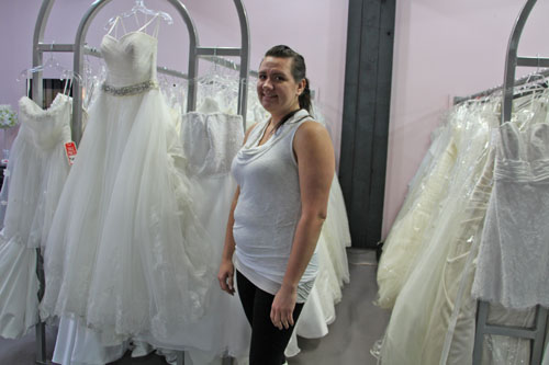 Owner of DebraDee Weddings Naomi Braun stands next to their wedding dress collection.