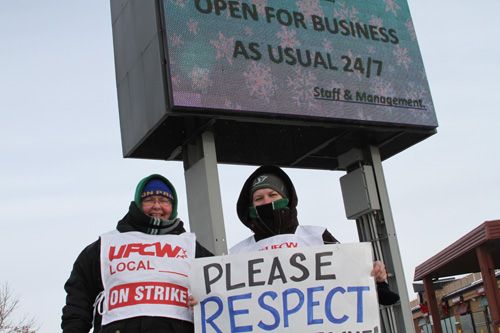 Laureen Smith (pictured left) stands with a union representative on the picket line.