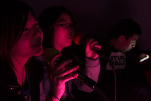 Lorraine Liu, left, and Rae Ming, right, both 18 and ESL students from China, sing a Chinese love song at SweeTea Cafe on Victoria Avenue, while their friend Jacob Lee, 23, waits his turn on his cellphone. SweeTea Cafe, which opened in August, is one of two karaoke bars in Regina. Photo by Adam Gamble.